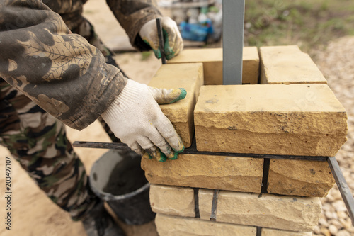 Fototapeta man builds a brick wall at a construction site