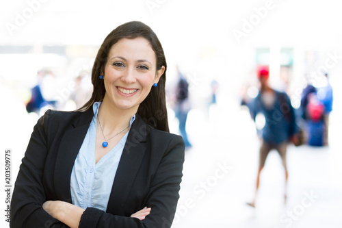 Urban girl standing out from the crowd at a city street. Businesswoman posing confident and smiling