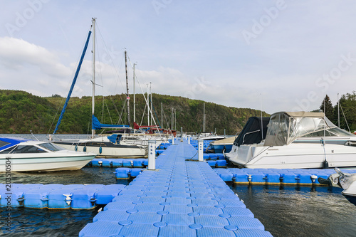Plastic pontoon pier leading to to anchored yachts and sailing boats.