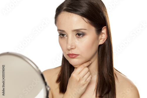 a sad woman touches her neck on the mirror