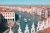 View of the Grand Canal with sailing ships, houses with red roofs and mountains in the distance, a bright sunny day in Venice, Italy.