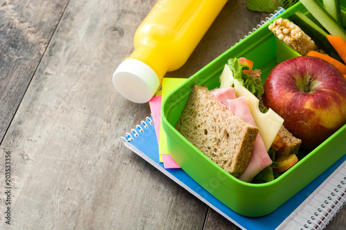 Healthy school lunch: Sandwich, vegetables ,fruit and juice on wooden table. Copyspace © chandlervid85