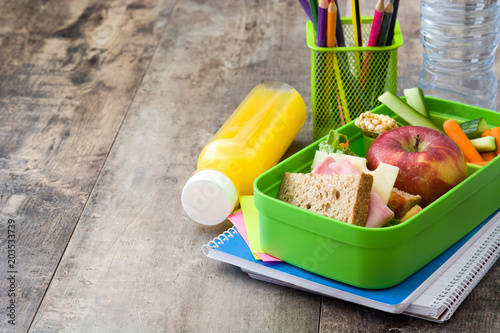 Healthy school lunch: Sandwich, vegetables ,fruit and juice on wooden table. Copyspace