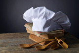 Old culinary books , chef hat and wooden spoons . - 203536316