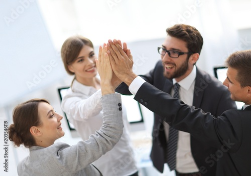 successful business team giving each other a high-five, standing in the office