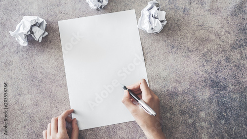 Hand writing on blank paper with crumpled paper ball