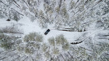Aerial view on SUV 6x6 that rides by winter road in snow-covered forest