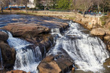 View from the bridge at a beautiful waterfall in the middle Falls park in the downtown. Greenville, SC, USA