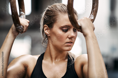 Focused young woman working out on rings at the gym
