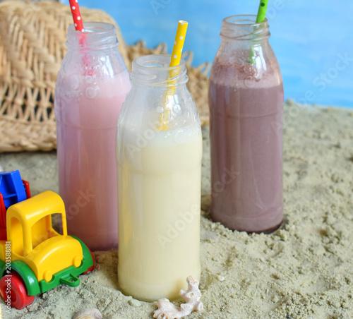 Plexiglas Milkshake Three bottle of various milkshakes (chocolate, strawberry and vanilla). Healthy smoothie with straw. Tasty milk shake cocktails. Refreshing summer drink on yellow sand summer beach. Copy space