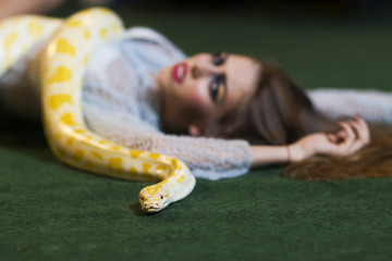 Girl with long hair and albino python. Girl with makeup face and yellow snake © tverdohlib