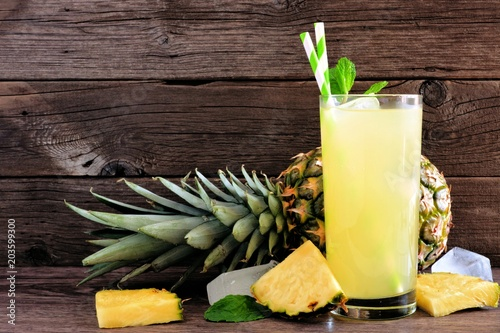 Fototapeta Glass of pineapple juice. Side view on a rustic wood background,