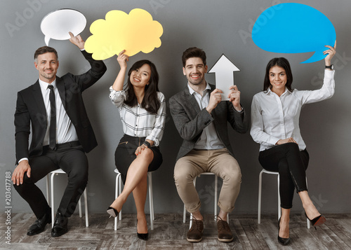 Fototapeta smiling multiethnic business people with paper chat bubbles and arrow waiting for job interview