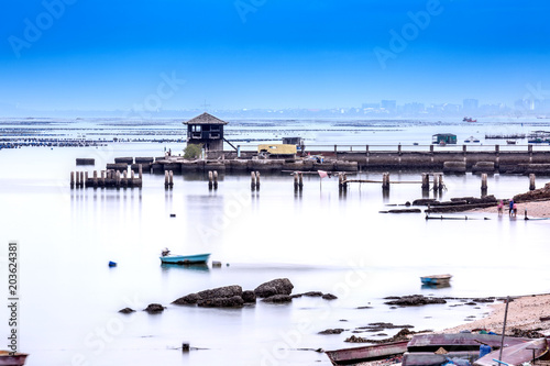 small tower on fishing pier with smooth blue sea and reflection of sky like mirror, coast line of Sriracha Thailand, long exposure