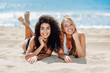 Leinwandbild Motiv Two young women with beautiful bodies in swimsuit on a tropical beach