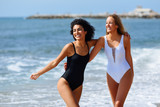 Two young women with beautiful bodies in swimsuit on a tropical beach