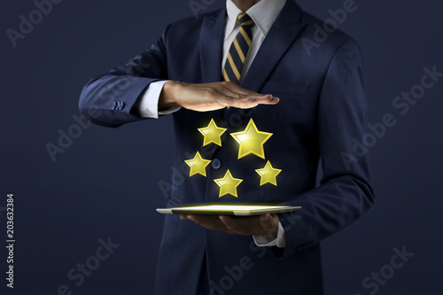 Increase rating, ranking, review, evaluation or classification concept. Businessman is showing five stars rating that projected from tablet on dark tone background.