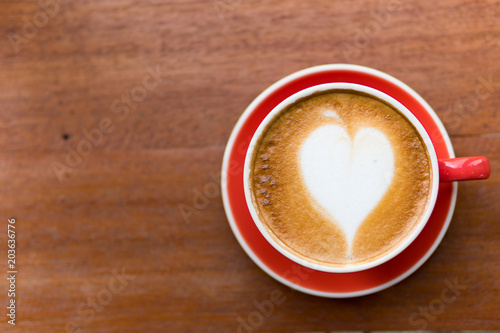 Red cup of coffee with latte art heart shape,soft focus design for valentine background