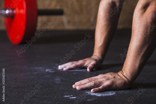 Crop hands on floor near barbell