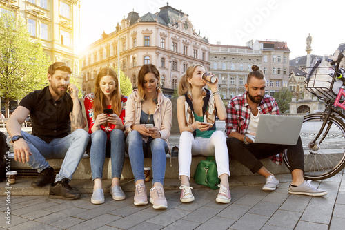 Glückliche Studenten genießen ihren sorglosen Lebensstil in der Stadt sitzen auf der Straße mit Gadgets an einem sonnigen Nachmittag