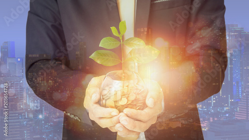 Foto Murales Businessman hand putting the coins and plant on the glass. Double exposure ofconcept of saving money for finance accounting, growing business
