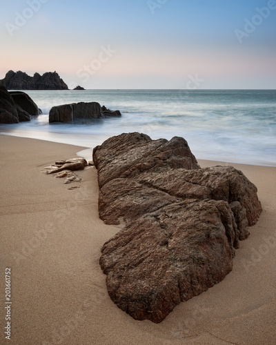 Fotobehang Blauwe hemel Stunning vibrant sunrise landscape image of Porthcurno beach on South Cornwall coast in England