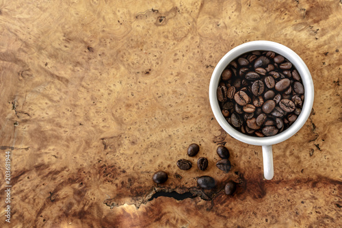 coffee beans in white cup on wooden background, Top view.
