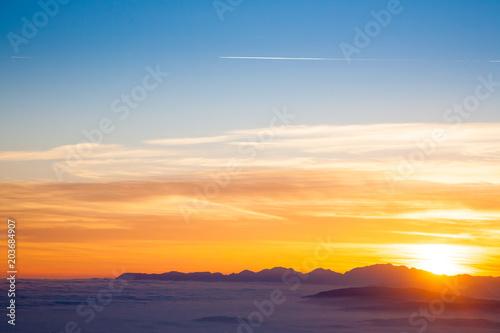 Fotobehang Oranje Mountain silhouette at sundown
