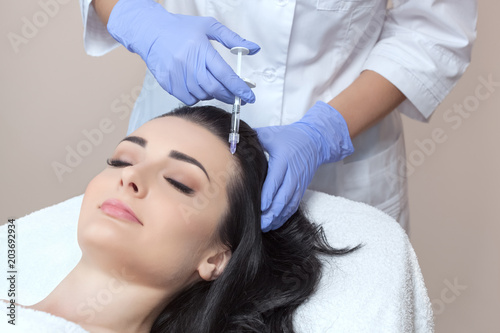 Procedure of mesotherapy. The doctor cosmetologist makes the procedure of mesotherapy in woman's head. Strengthen hair and their growth. © Dimid