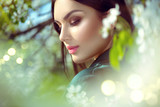 Beauty young woman enjoying nature in spring apple orchard, Happy Beautiful brunette girl in Garden with blooming apple trees. Smiling Person smelling blossom flowers outdoors. Fashion model portrait