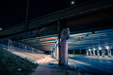 Gritty dark city highway bridge and street underpass at night © Bruno Passigatti