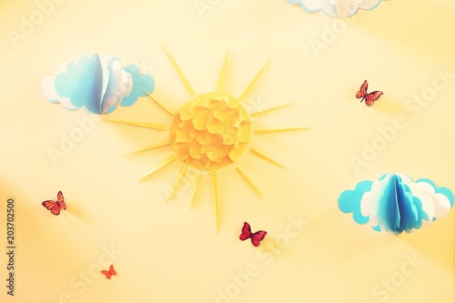 Fototapeta The decoration of the wall in the nursery with paper clouds, sun and butterflies