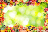 Frame of fruits and vegetables on abstract blurry plant background.