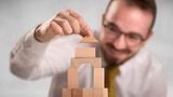 Young handsome businessman using wooden building blocks  - 203741784