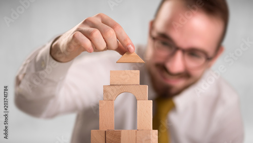 Fototapeta Young handsome businessman using wooden building blocks