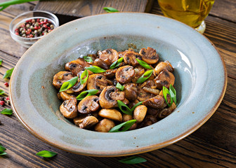 Baked mushrooms with soy sauce and herbs. Vegan food.