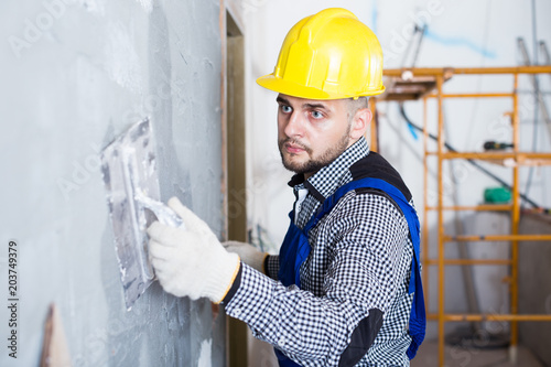 Professional in the helmet is plastering the wall © JackF