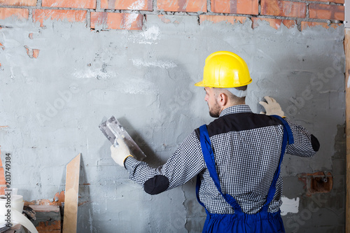 Professional builder in the helmet is plastering the wall