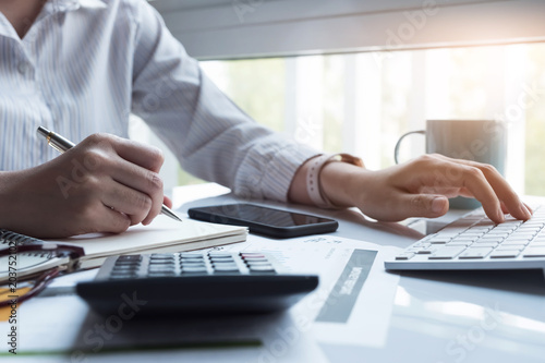 Business women using computer and calculator during note some data on notepad for calculate financial at home office