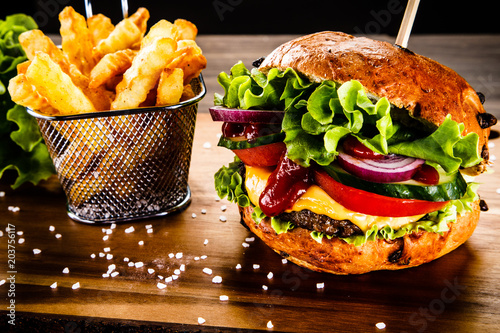 Tasty burger with chips served on cutting board - 203756117