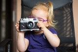 Little girl making photo with vintage camera - 203761385
