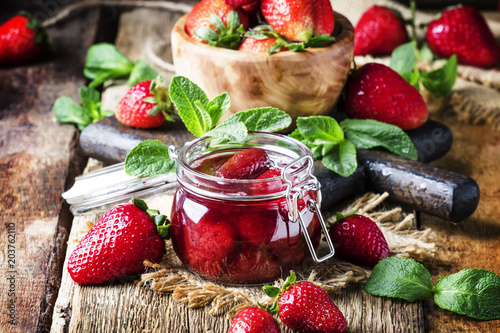 Strawberry jam, vintage wood background, selective focus