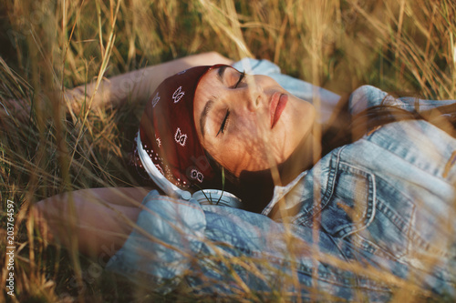 Canvas Muziek Closeup of young woman listens to music and lying in the meadow
