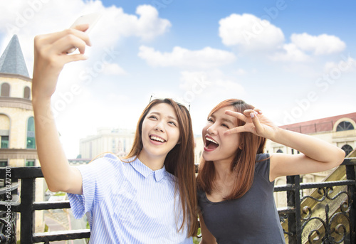 Fototapeta two happy girls taking selfie and travel concept