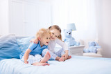 Kids playing in white bedroom - 203778327