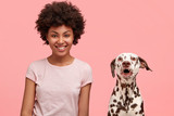 Lovely mixed race female with Afro hairstyle, being in good mood after stroll with favourite dalmatian dog, looks positively at camera, feels refreshed and full of energy, isolated on pink wall