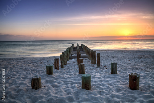 Plexiglas Strand Ruins of the old Naples Pier at sunset on the ocean