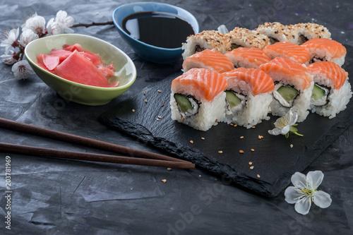 Fotobehang Sushi bar Philadelphia rolls with salmon, avocado, eel on stone black background. Sushi rolls, japanese food.