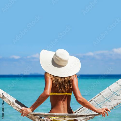 Fototapeta Woman in sunhat swinging in hummock