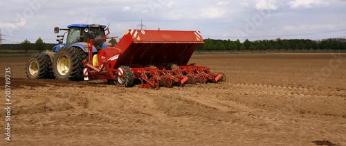 Aluminium Trekker Blauer Traktor mit rotem Anhänger auf dem Acker